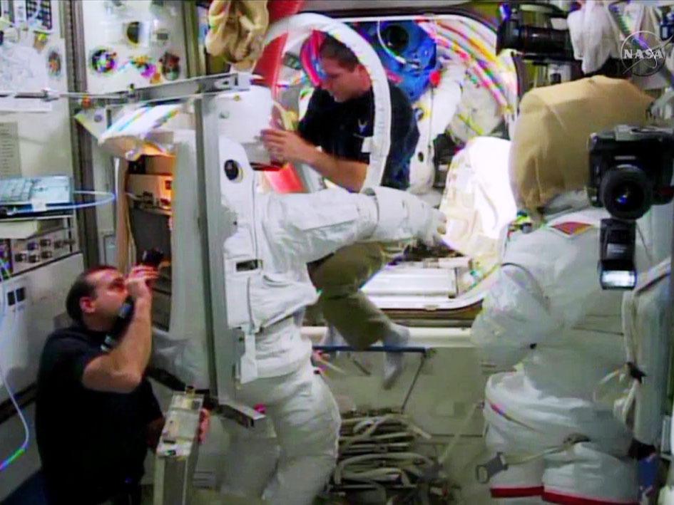 Два космонавта готовятся к выходу в открытый космос